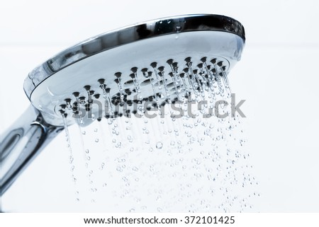 Clear water flowing from shower in a bathroom - stock photo