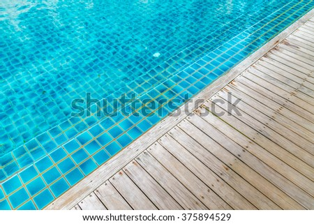 clear water in swiming pool and wooden walkway - stock photo