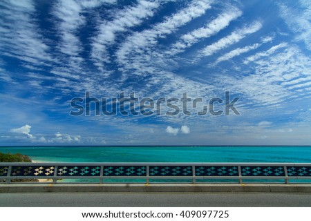 Clear water, striped clouds, and clear sky on Ikema Ohashi Bridge in Miyakojima, Okinawa, Japan - stock photo