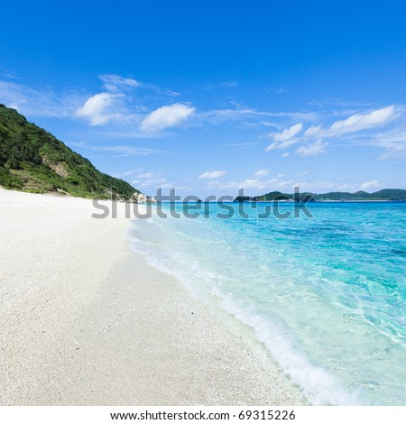Clear water waves calmly lapping onto a white sandy tropical beach on a coral island of Okinawa, Japan - stock photo