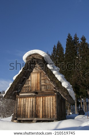 Clear winter day with blue sky and Japanese thatched-roof house - stock photo