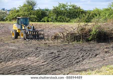 Clearing brush with a heavy loader for a retention pond area - stock photo