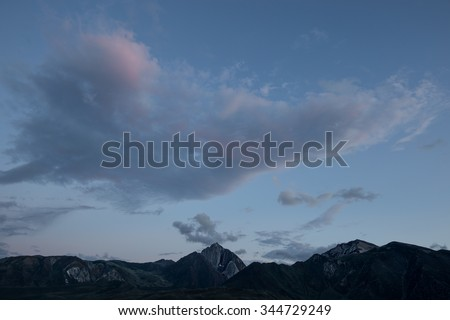 Clearing clouds at sunset over Mt Morrison in California's Eastern Sierra Nevada. - stock photo