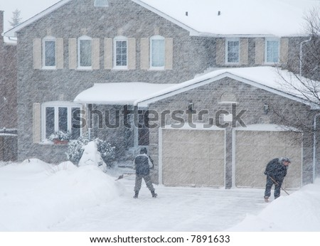 Clearing driveway in blizzard - stock photo