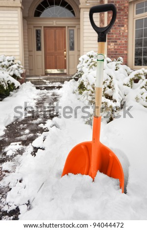 Clearing path to the front door after a big snowstorm - stock photo