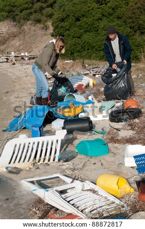 Clearing rubbish washed up onto a beach - stock photo