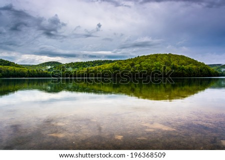 Clearing storm clouds over Long Pine Run Reservoir, in Michaux State Forest, Pennsylvania.
