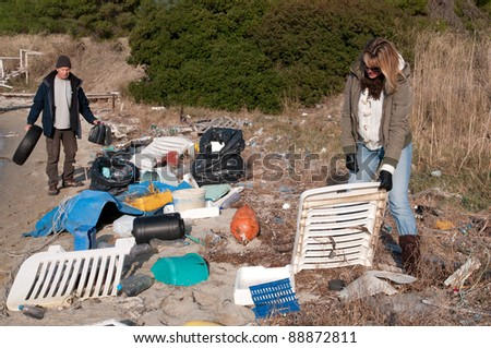 Clearing up rubbish washed up onto a small beach - stock photo