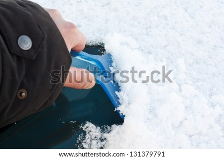 Clearing windscreen with ice scraper after heavy snow for safe winter driving on a frosty morning with copy space to the right - stock photo