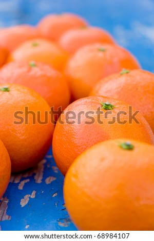Clementine fruits on blue background, close up