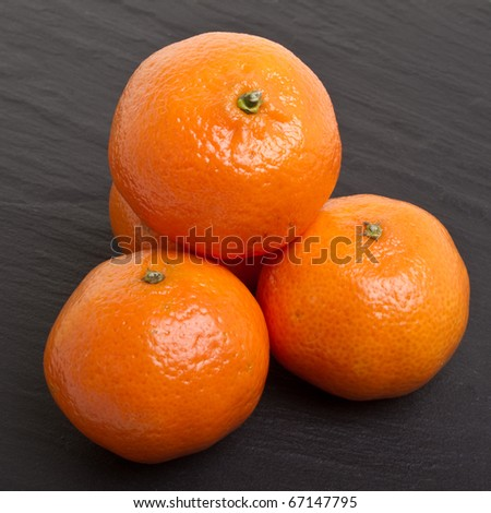 Clementines from low perspective isolated on dark grey slate background.