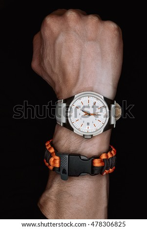 Clenched hand of man with watch and paracord wristband.