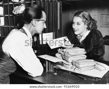 Clerk with woman mailing letter - stock photo