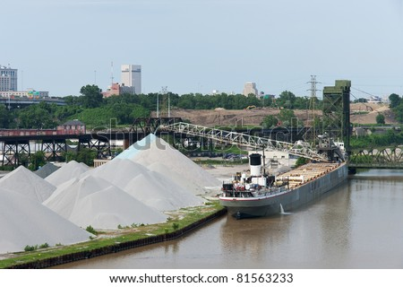 CLEVELAND - JULY 24: The bulk freighter Manistee off-loads aggregate material onto the bank of the Cuyahoga River on July 24, 2011 at Cleveland, Ohio - stock photo