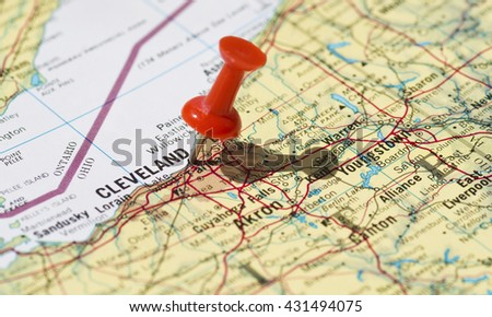 Cleveland marked on map with red pushpin. Selective focus on the word Cleveland and the pushpin. Pin is in an angle and casts some shadow to the right.  - stock photo