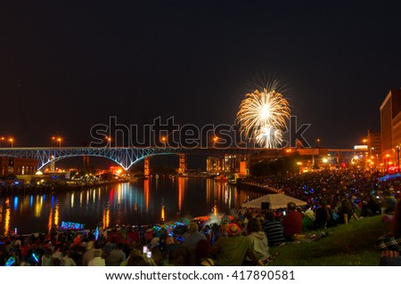 CLEVELAND, OH - JULY 4, 2015: Throngs of spectators gather along the banks of the Cuyahoga River to watch the spectacular Independence Day fireworks show downtown.