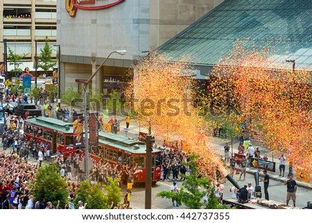 CLEVELAND, OH - JUNE 22, 2016: Confetti cannons signal the start of the Cavaliers NBA championship parade next to the Q with eager crowds thronging the route. - stock photo