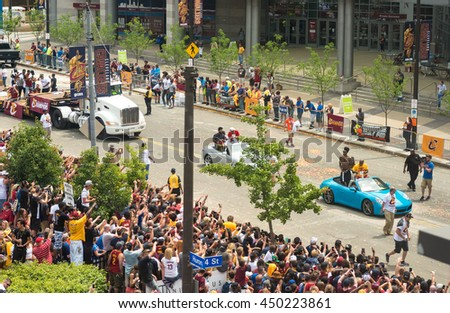 CLEVELAND, OH - JUNE 22, 2016: Imam Shumpert of the Cleveland Cavaliers (in turquoise car at right) is cheered by the crowds in the Cavs' NBA championship parade. - stock photo