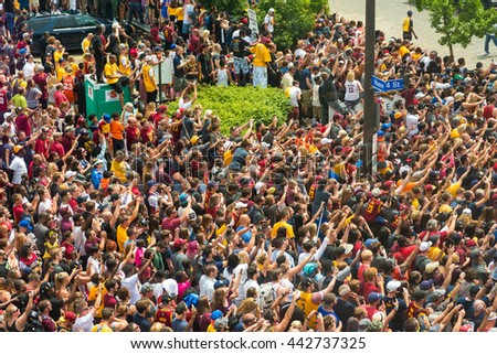CLEVELAND, OH - JUNE 22, 2016: Massive crowds cheer and wave in adulation as the NBA champion Cavaliers ride by in their history-making victory parade in downtown Cleveland. - stock photo