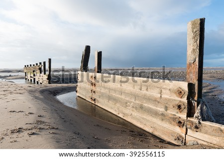 cleveleys, england, 02/17/2016, A rustic, weathered wooden sea defence wall, showing signs of damage.