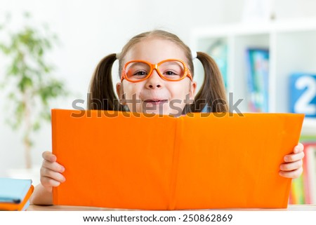 clever child girl behind of open book indoors - stock photo