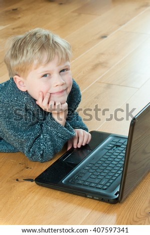 Clever child lying down and using a laptop - stock photo