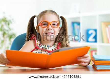 clever cu te child girl wered eyeglasses with book in primary school or home - stock photo