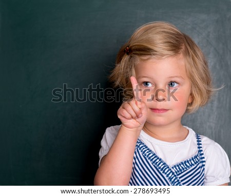 clever girl in front of black board with forefinger up - stock photo