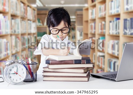 Clever little girl studying in the library while writing on the book with laptop and alarm clock on the table - stock photo