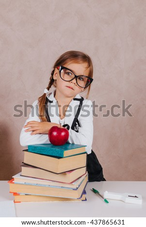 Clever little schoolgirl in glasses at table with books trying to learn new skills - stock photo