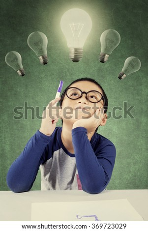 Clever male student thinking idea while sitting under bright light bulb and holding a pen - stock photo