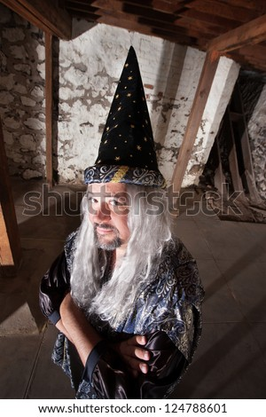 Clever man dressed as a wizard with long hair - stock photo