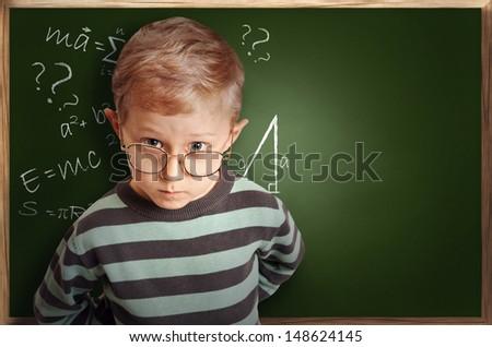 Clever pupil boy in eyeglasses near green school board  - stock photo