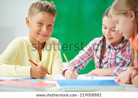 Clever schoolboy looking at camera at lesson of drawing with two girls near by - stock photo
