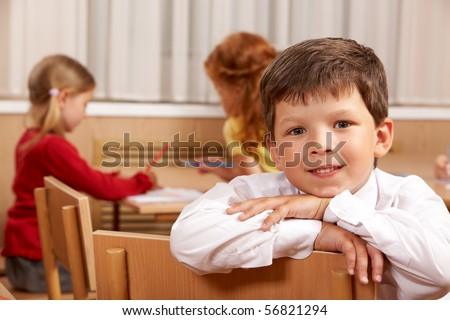 Clever schoolboy looking at camera in classroom with his classmates at background - stock photo