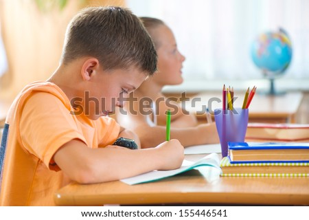 Clever schoolboy studying in classroom at school - stock photo