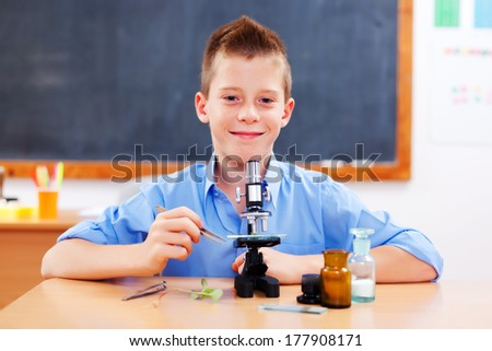 Clever schoolboy with microscope in biology class