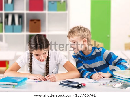 Clever schoolgirl writing a test and her friend looking at her copybook  - stock photo