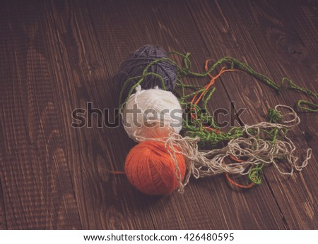 Clews of threads are on the wood table. They are of different colors - stock photo