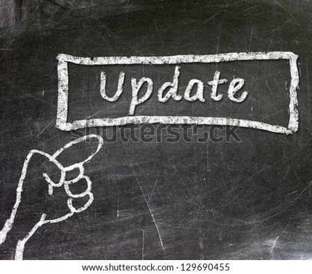click finger update mark on the black chalkboard - stock photo