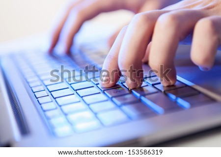 Click! Hands of a man on a keyboard with blue backlighting. - stock photo