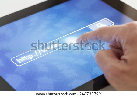 Clicking on a tablet with internet address and search button - stock photo