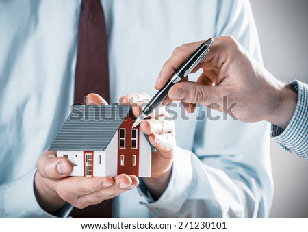 Client discussing a house design with an architect pointing to the model of the house with his pen, close up of their hands - stock photo