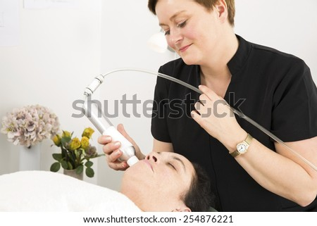 Client get face treatments at beauty clinic - stock photo