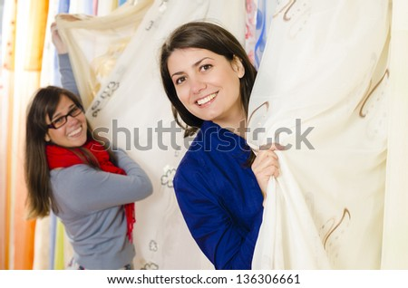 Client in a textiles shop choosing draperies - stock photo