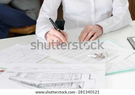 Client signing a real estate contract in real estate agency - stock photo