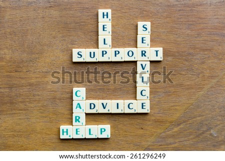 Client support crossword blocks on the wooden background - stock photo