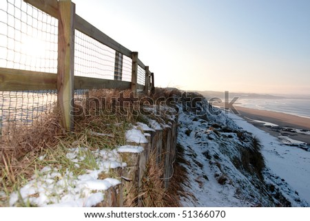 cliff edge fence over a beach on a cold winters day - stock photo