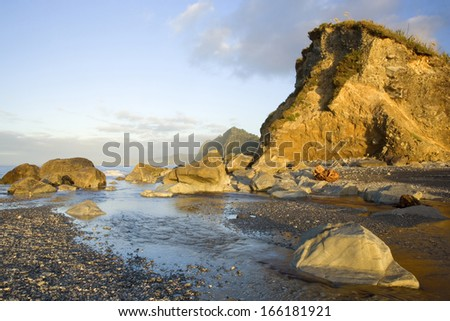 cliffs and rocks at Gillespies Beach in last evening light, Westland National Park, West Coast, South Island, New Zealand - stock photo