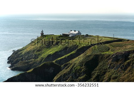 Cliffs in Howth and lighthouse, Ireland - stock photo